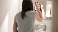 Young woman applying eyelid makeup in front of the mirror HD Stock Footage