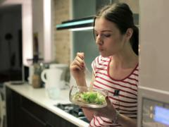 Young attractive woman eating salad in the kitchen NTSC - stock footage