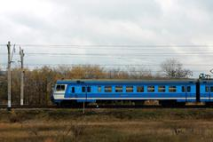 Electic train running by the rails on the fields Stock Photos