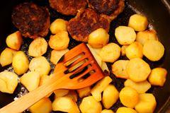 Seasoned potato slices in skillet pan in kitchen Stock Photos