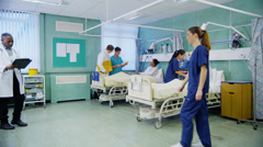 Medical staff working together and taking care of patients on a hospital ward - stock footage