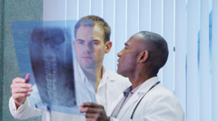 2 doctors looking at a medical x ray are discussing a patient's condition. Stock Footage