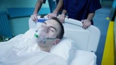Hospital emergency team rush a patient on a gurney to the operating theatre. Stock Footage