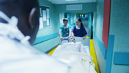 Stock Video Footage of Hospital emergency team rush a patient on a gurney to the operating theatre.