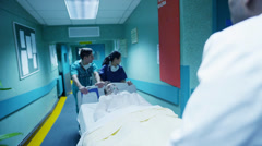 Hospital emergency team rush a patient on a gurney to the operating theatre. - stock footage
