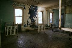 delapidated hospital building with empty rusted beds - stock photo