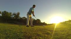 Man Hits Tee Shot Golfing At Sunset - stock footage