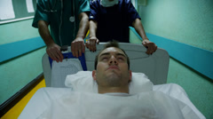 Medical staff transport a patient in serious condition on a hospital gurney - stock footage