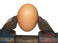 egg is clamped in the old vice, isolated on a white background - stock photo