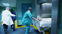 Hospital emergency team rush a patient on a gurney to the operating theatre Stock Footage