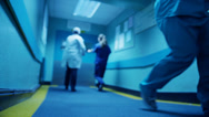 Stock Video Footage of Hospital emergency team rush a patient on a gurney to the operating theatre