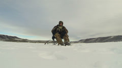 Ice fishing frozen lake man picks up pole HD 0228 Stock Footage