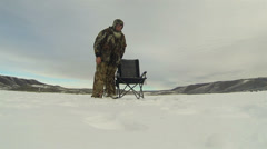 Ice fishing frozen lake sitting by hole HD 0228 Stock Footage
