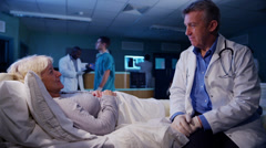 Caring hospital doctor chatting at the bedside of elderly female patient at nigh Stock Footage