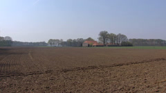 Farmhouse behind plowed field + pan country road, Gelderland Stock Footage