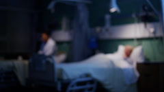 Elderly female patient resting in bed with medical team working in the backgroun Stock Footage