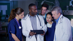 Hospital doctor with computer tablet has a discussion with other medical staff. Stock Footage