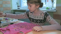 Young girl paints on the shirt Stock Footage