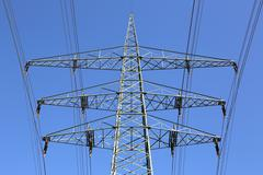 electricity pylons and lines against blue sky energy topic - stock photo