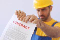 Builder ripping up a contract - stock photo