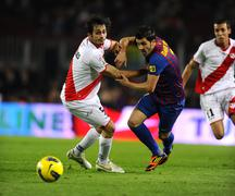 Alejandro Arribas of Rayo Vallecano vies with David Villa of FC Barcelona - stock photo