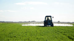 Tractor spray field with herbicide and insecticide chemicals Stock Footage