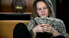 Girl studies dollar bank notes with consideration Stock Footage