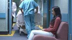 Worried young woman sitting alone in a hospital waiting area waits for news. - stock footage