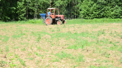 Farmer drive retro tractor sow buckwheat seeds in field Stock Footage