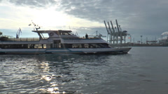 Port of Hamburg - Ferry in backlight overtaking in front of the crane Stock Footage