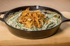 fried onions with beans in a cast iron skillet - stock photo