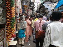 indian women in colorful saris browse the market stores - stock photo