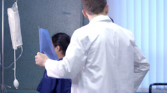 Medical team working together and checking a patient's x-ray. - stock footage