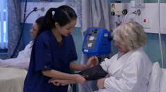 Caring nurse checks an elderly female patient's blood pressure Stock Footage