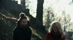 Girls throw leaves high into the air at the same time shot in slow motion - stock footage