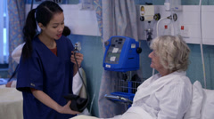 Caring nurse chats with an elderly female patient on a hospital ward. - stock footage