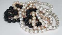 Black, pink and white pearls necklaces turning close up Stock Footage