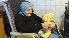 Senior woman joking with a vintage teddy bear Stock Footage
