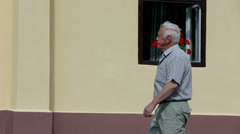 Old man opens the door and enters the building Stock Footage