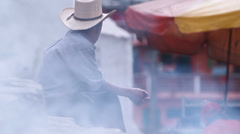 Third world country. Man is sitting in the smoke Stock Footage