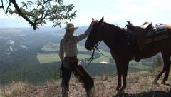 COWGIRL OVERLOOKING VALLEY WITH HORSE Stock Footage