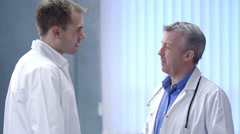 Two doctors on a hospital ward having a discussion. Stock Footage