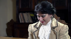 Upper body of woman dressed in 19th century clothes playing piano Stock Footage