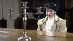 Female in 18th century clothes playing piano Stock Footage