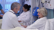 Stock Video Footage of Caring doctor chats with an elderly female patient on a hospital ward.