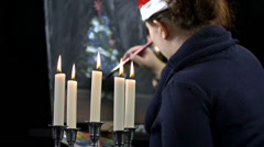 Stock Video Footage of Candlestick and female artist with Santa hat drawing