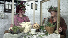 Two ladies sit at the table full of flowers holding a frame in their hands Stock Footage