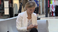 Attractive young girl texting in shopping mall - stock footage