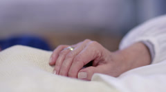 Close up holding the hand of an elderly patient in hospital bed. No faces can be Stock Footage