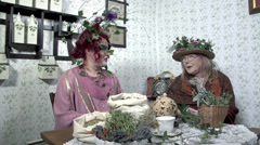 Two ladies made-up in plant theme sit at the table Stock Footage
